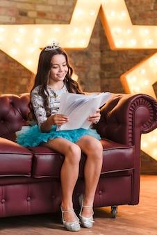 Sonriente niña linda sentada en el sofá leyendo guiones en el backstage