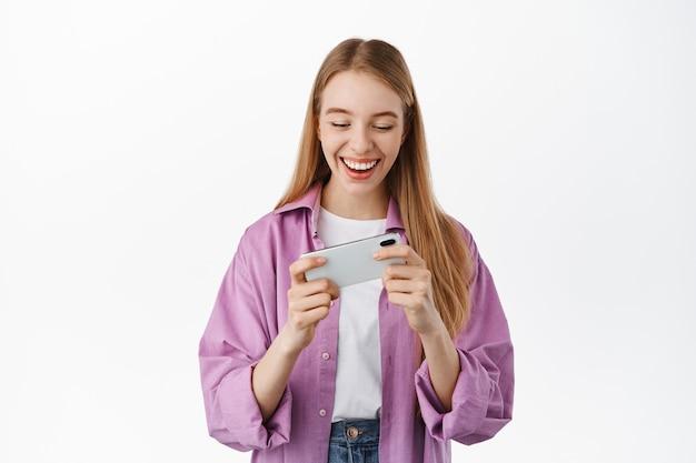 Sonriente niña moderna sosteniendo el teléfono inteligente en ambas manos, mirando la pantalla móvil horizontal, viendo videos en el teléfono o jugando videojuegos, de pie sobre una pared blanca