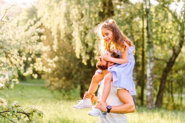Sonriente niña montando en los hombros del padre en el parque