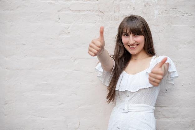 Sonriente niña morena con el pelo largo con un vestido blanco muestra un signo de clase con un pulgar levantado sobre un fondo de ladrillo macizo. lugar para tu diseño