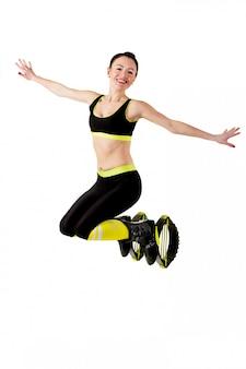 Sonriente niña morena saltando en un kangoo salta zapatos.