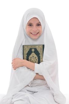 Sonriente niña musulmana ama el libro sagrado del corán