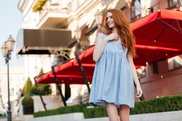 Sonriente niña pelirroja de pie afuera en una calle de la ciudad
