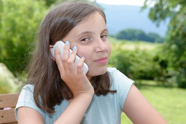 Sonriente niña pre adolescente llamando en teléfono inteligente, al aire libre