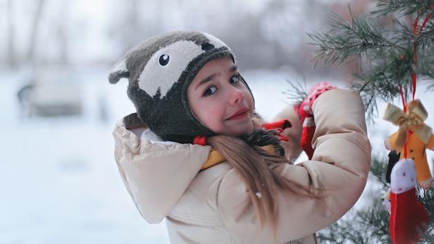 Sonriente niña de preescolar en sombrero divertido y abrigo decorando un pino con juguete artesanal entre bosque de invierno,