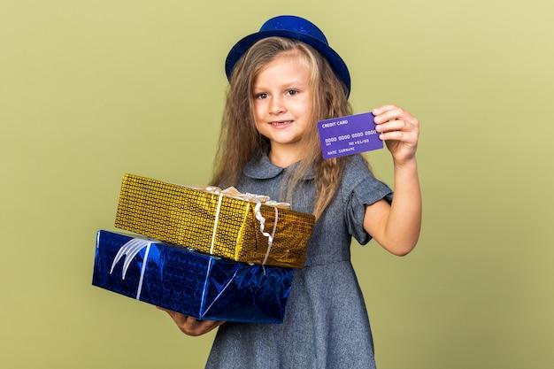 Sonriente niña rubia con gorro de fiesta azul sosteniendo cajas de regalo y tarjeta de crédito aislado en la pared verde oliva con espacio de copia