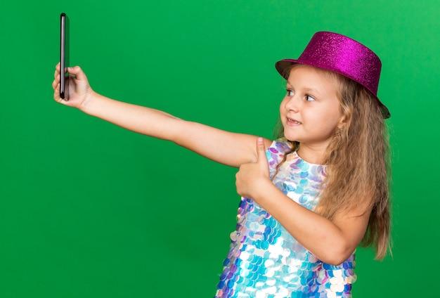 Sonriente niña rubia con gorro de fiesta púrpura pulgar hacia arriba tomando selfie en teléfono aislado en la pared verde con espacio de copia