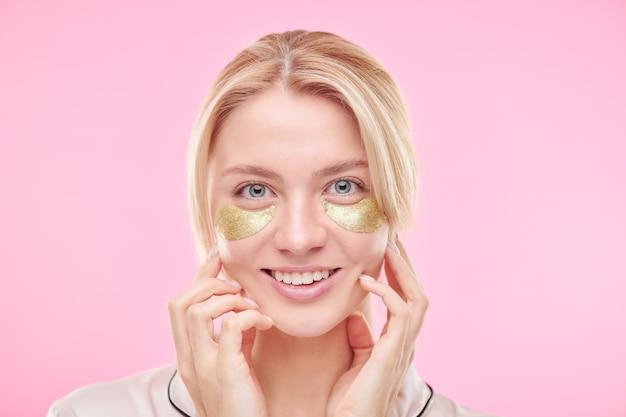 Sonriente niña rubia con parches dorados revitalizantes debajo de los ojos tocando su rostro mientras está de pie contra la pared rosa