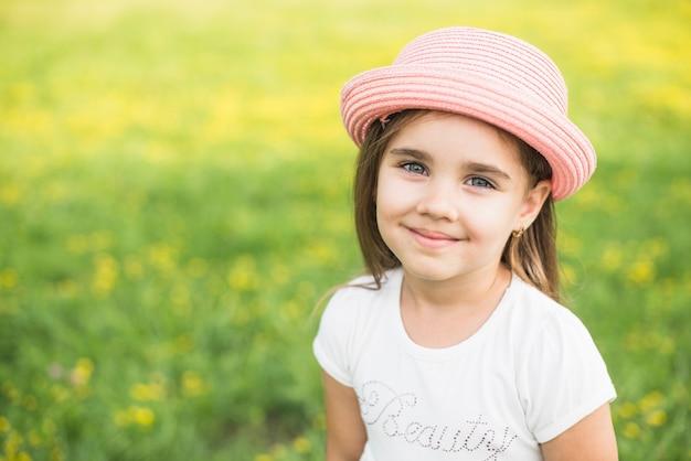 Sonriente niña con sombrero rosa en la cabeza en el parque