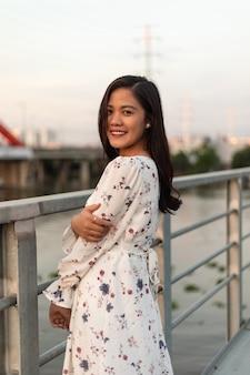 Sonriente niña vietnamita de pelo negro de pie sobre un puente