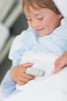 Sonriente niño acostado en una cama médica