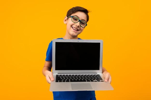Sonriente niño caucásico muestra la pantalla del portátil en amarillo con espacio de copia