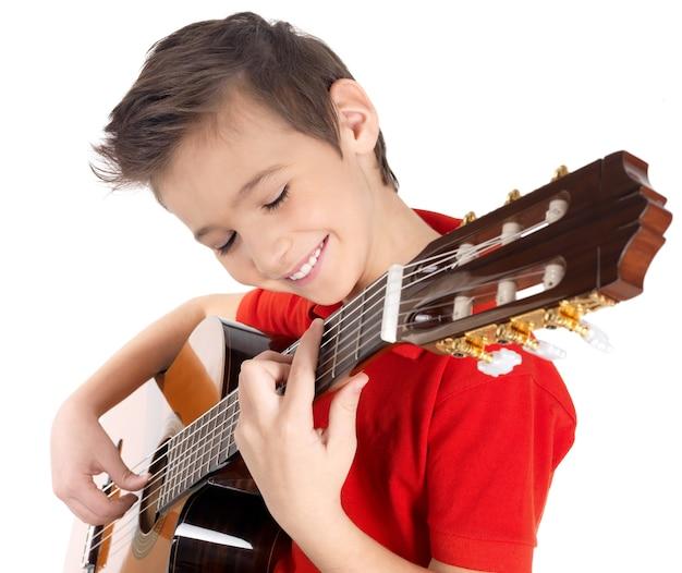 Sonriente niño caucásico está tocando la guitarra acústica - aislada en la pared blanca