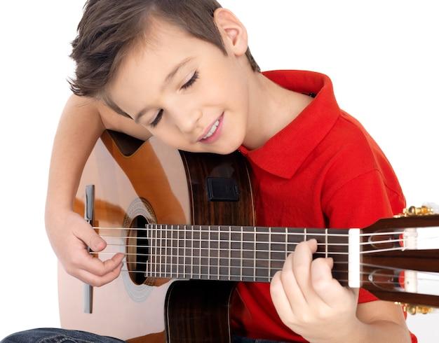 Sonriente niño caucásico está tocando la guitarra acústica - aislada sobre fondo blanco