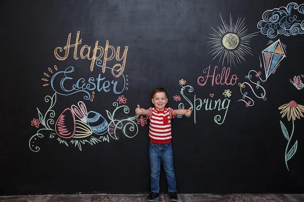 Sonriente niño feliz de pie y mostrando los pulgares para arriba