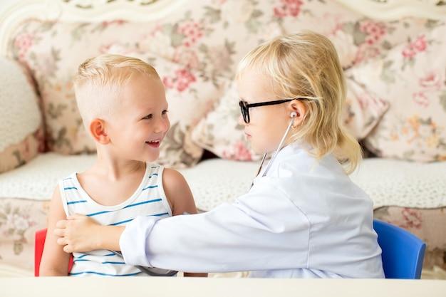Sonriente niño y una niña seria jugando al médico