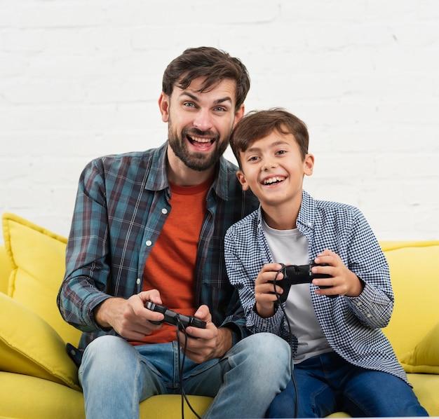 Sonriente niño y padre jugando en la consola