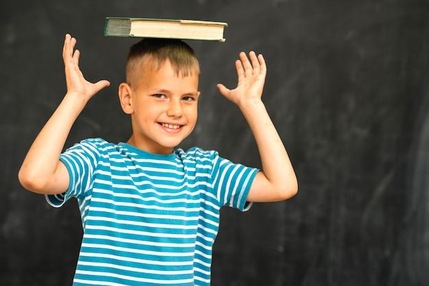 Sonriente niño posando con el libro