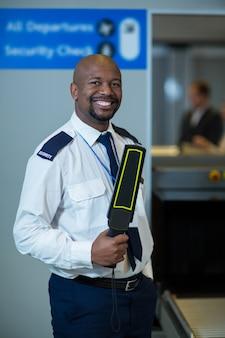 Sonriente oficial de seguridad del aeropuerto con detector de metales en la terminal del aeropuerto