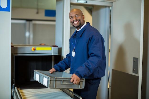 Sonriente oficial de seguridad del aeropuerto sosteniendo una caja cerca de la cinta transportadora