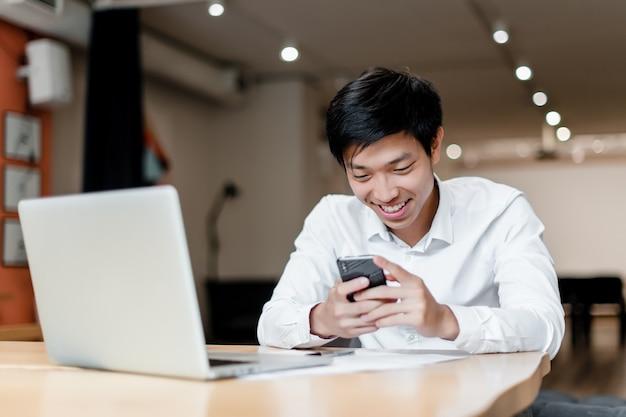 Sonriente oficinista asiático utiliza teléfono y computadora portátil