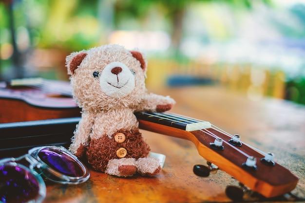 Sonriente oso de peluche muñeca con ukelele y gafas de sol