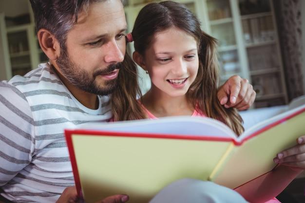Sonriente padre e hija mirando el álbum de fotos en la sala de estar