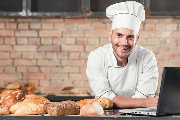 Sonriente panadero masculino con diferentes tipos de panes horneados y portátil en la encimera de la cocina