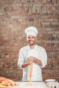 Sonriente panadero masculino de pie detrás de la mesa con masa y pan