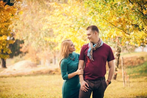 Sonriente pareja abrazándose en el parque otoño