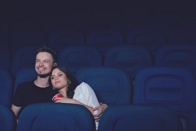 Sonriente pareja abrazándose y viendo películas divertidas en el cine