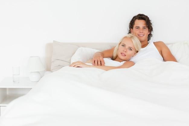 Sonriente pareja acostada en una cama