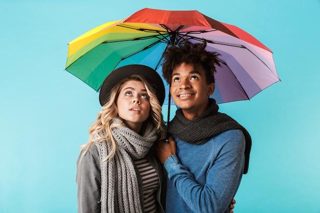 Sonriente pareja de adolescentes multirraciales vistiendo ropa de invierno de pie bajo un paraguas aislado sobre la pared azul
