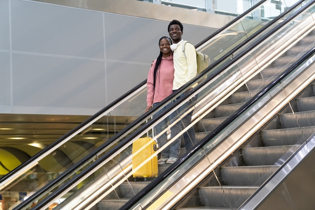 Sonriente pareja africana en el aeropuerto de pie en la escalera mecánica con maleta viaje después del cierre del covid final
