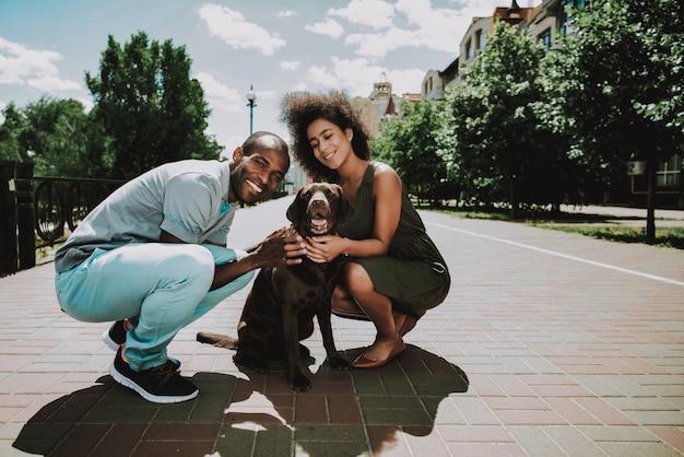 Sonriente, pareja americana africana, caricias, perro