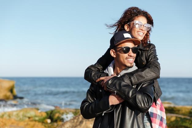 Sonriente pareja amorosa africana caminando al aire libre en la playa