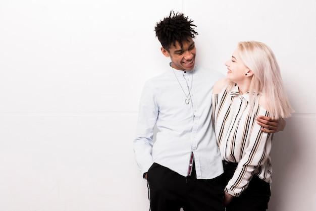 Sonriente pareja amorosa interracial abrazando de pie contra la pared blanca