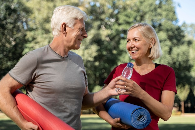 Sonriente pareja de ancianos al aire libre con colchonetas de yoga y botella de agua