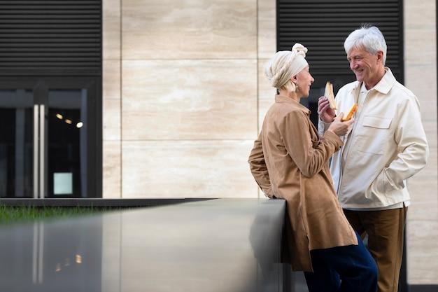 Sonriente pareja de ancianos al aire libre disfrutando de un sándwich juntos