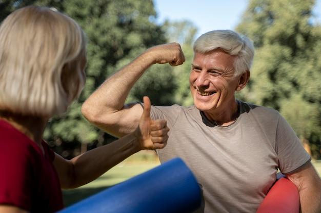 Sonriente pareja de ancianos al aire libre con esteras de yoga