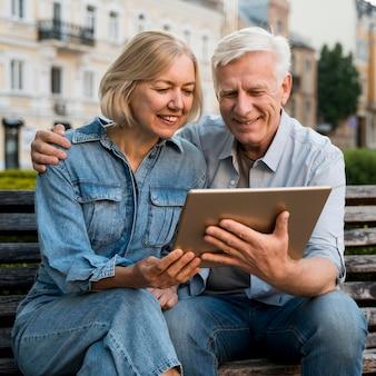 Sonriente pareja de ancianos mirando algo en tableta