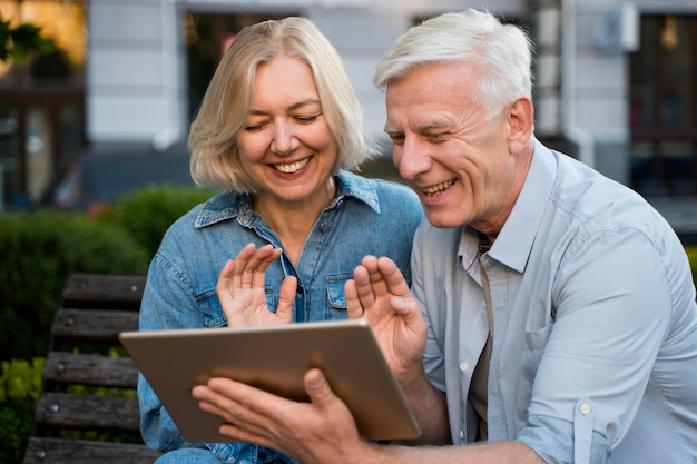 Sonriente pareja de ancianos saludando a alguien con quien están hablando en tableta