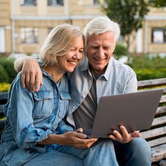 Sonriente pareja de ancianos sentados en un banco al aire libre con un portátil