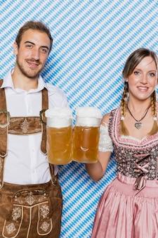 Sonriente pareja bávara con jarras de cerveza