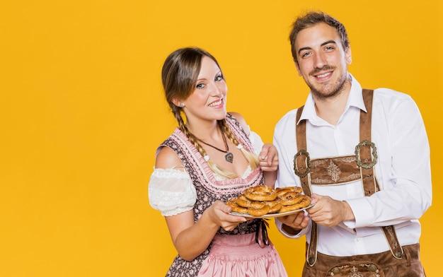 Sonriente pareja bávara con pretzels