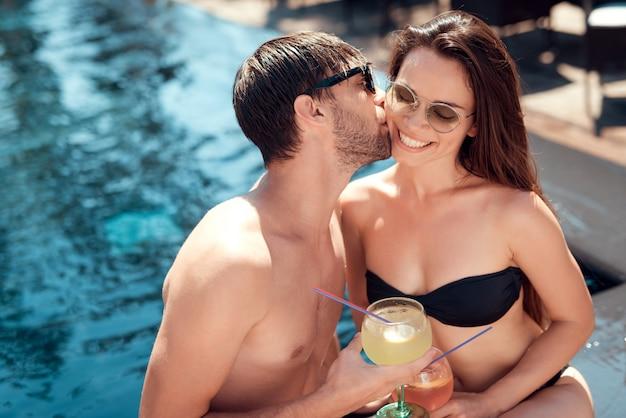 Sonriente pareja bebiendo cócteles en la piscina