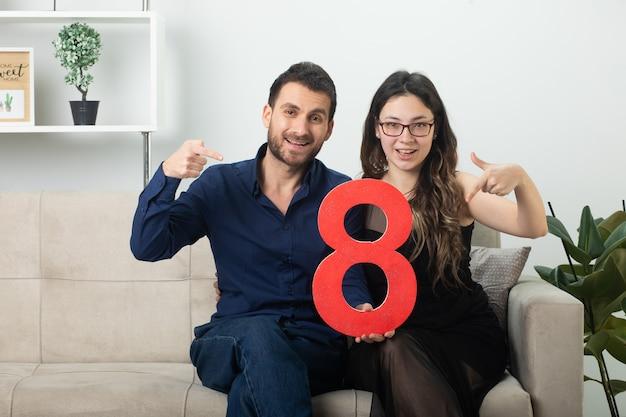 Sonriente pareja bonita sosteniendo y apuntando a la figura roja de ocho sentados en el sofá en la sala de estar en el día internacional de la mujer de marzo