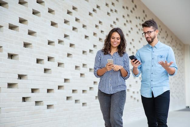 Sonriente pareja caminando y usando teléfonos inteligentes