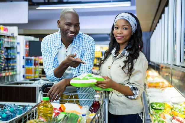 Sonriente pareja de compras en la sección de comestibles en el supermercado