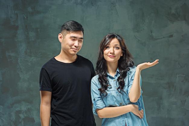 Sonriente pareja coreana en gris